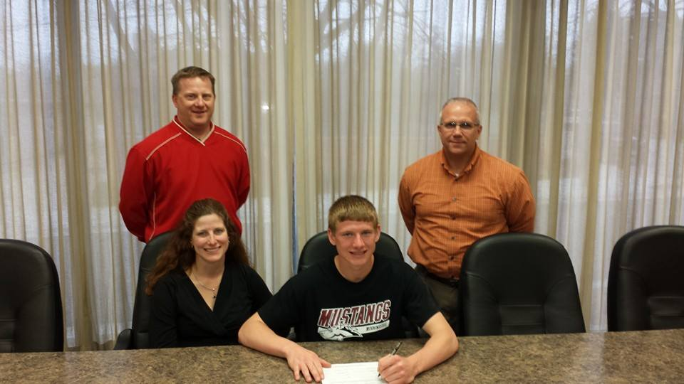 Grant Lehmann signs his national letter of intent, with mother Cindi and father Darwin looking on. At right is Forest City Boys Track Coach Ken Kasper