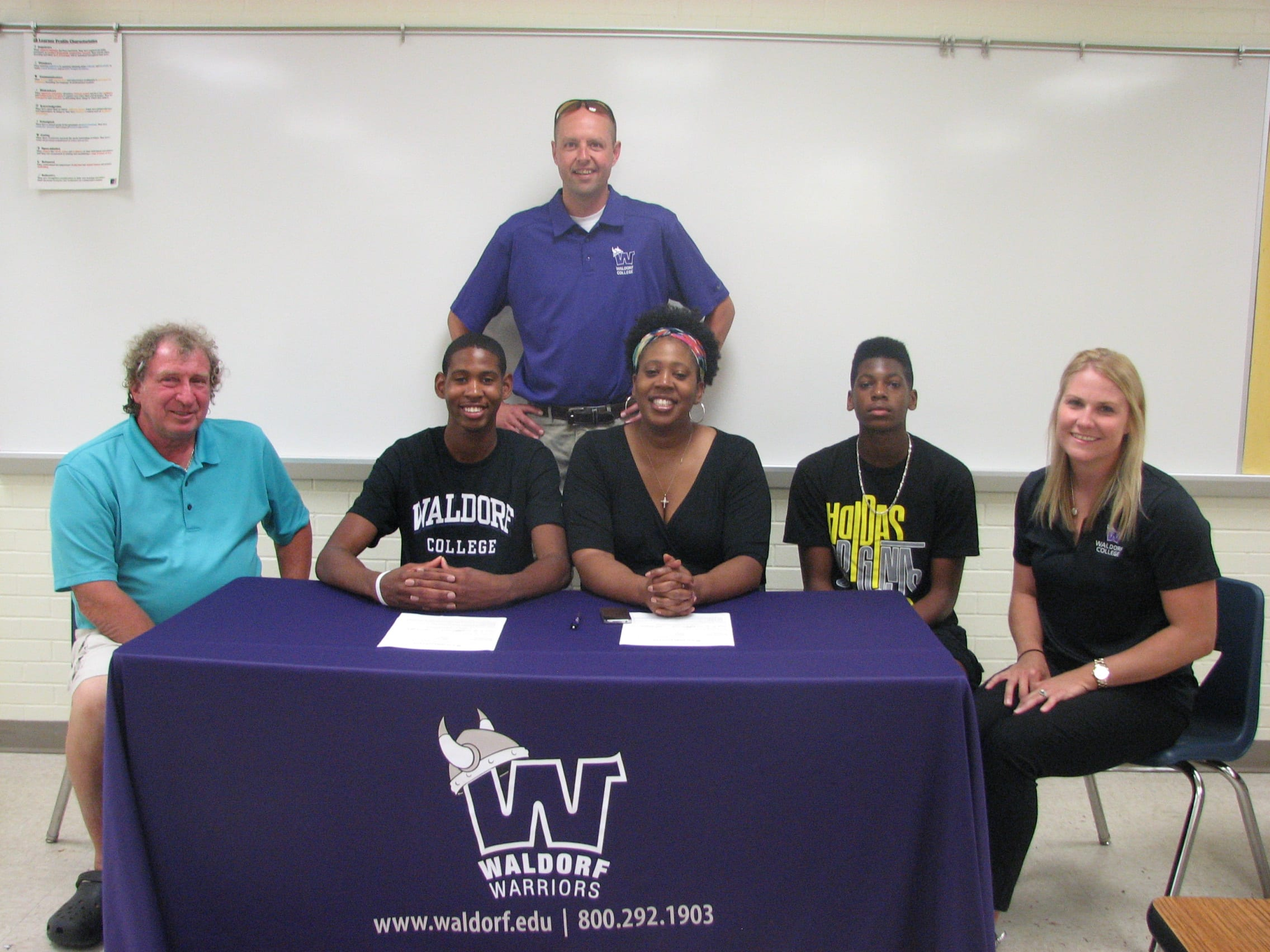 Pictured in back, Waldorf head coach Kendrick Clay. In front, from left, Park Center coach Bruce Smith; Henderson; Henderson's mother, Yvette and brother, Devin, and Waldorf associate head coach Kelsey Olson.